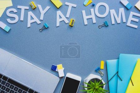 Photo pour Vue du dessus du lettrage de séjour à la maison près des appareils numériques et de la papeterie sur la surface bleue - image libre de droit