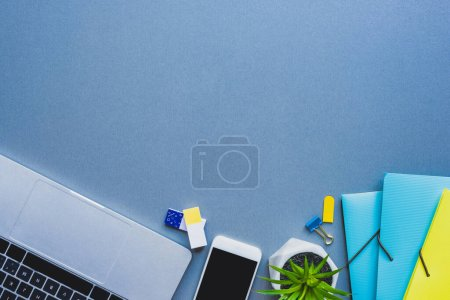 Photo for Top view of laptop, smartphone and plant near stationery on blue surface - Royalty Free Image