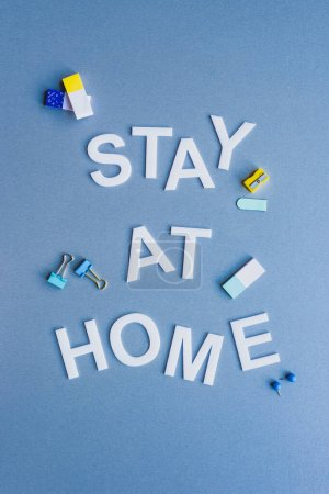 Photo for Top view of stay at home lettering near erasers, binder clips and pencil sharpener on blue surface - Royalty Free Image