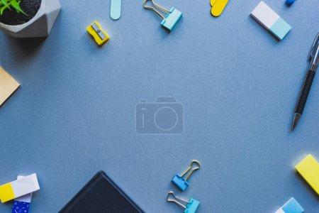 Photo pour Vue du dessus du cadre depuis la papeterie et la plante sur fond bleu - image libre de droit