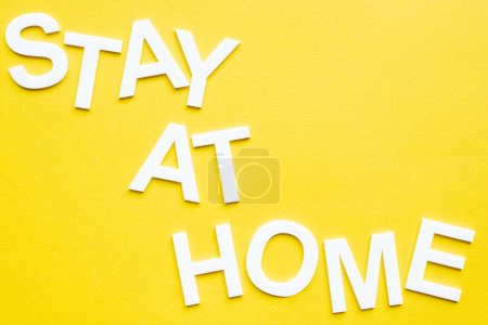 Photo for Top view of lettering stay at home on yellow surface - Royalty Free Image
