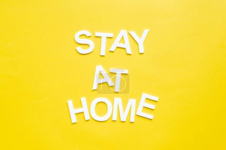 Top view of stay at home lettering on yellow surface