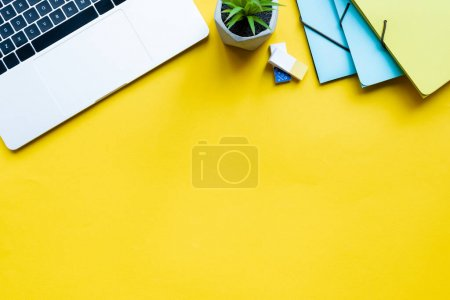 Photo for Top view of laptop, plant and office supplies on yellow surface - Royalty Free Image