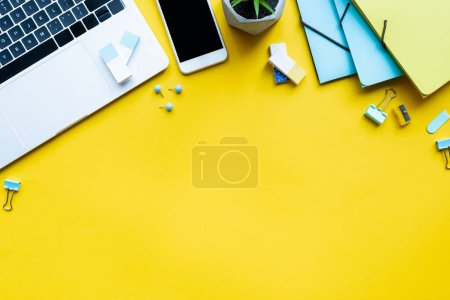 Top view of digital devices near plant and stationery on yellow background