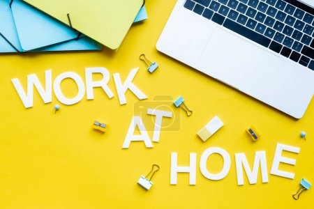 Photo for Top view of work at home lettering near laptop and stationery on yellow background - Royalty Free Image