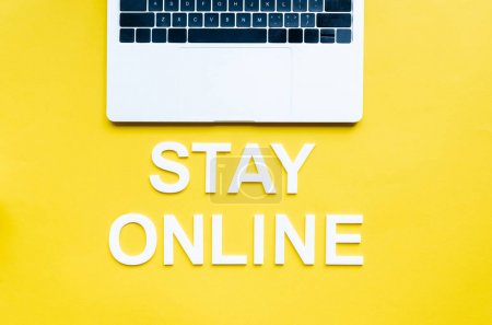 Top view of stay online lettering and laptop on yellow surface