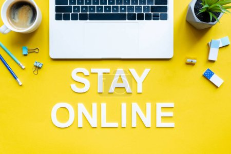 Photo for Top view of stay online lettering near laptop, coffee and stationery on yellow background - Royalty Free Image