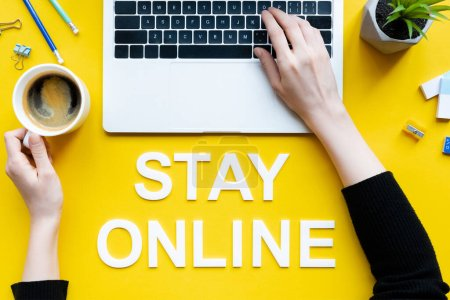 Photo for Top view of lettering stay online and woman using laptop and holding coffee on yellow surface - Royalty Free Image