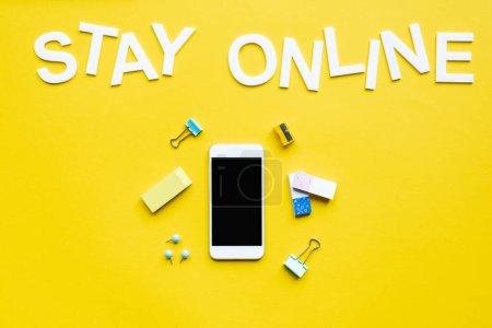 Foto de Vista superior del teléfono inteligente con pantalla en blanco cerca de la papelería y permanecer en línea de la carta en la superficie amarilla. - Imagen libre de derechos
