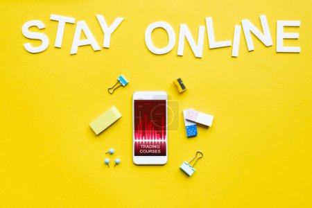 Photo for Top view of smartphone with trading courses app, office supplies and stay online lettering on yellow surface - Royalty Free Image