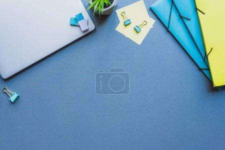 Photo pour Vue du dessus de l'ordinateur portable, des dossiers en papier et de la papeterie sur fond bleu - image libre de droit