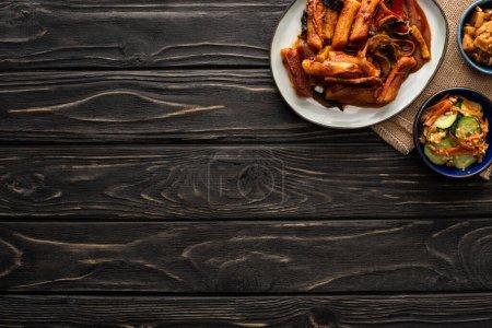Photo pour Vue de dessus de topokki épicé près de pommes de terre coréennes braisées, concombres marinés, baguettes et serviette de coton sur la surface en bois - image libre de droit