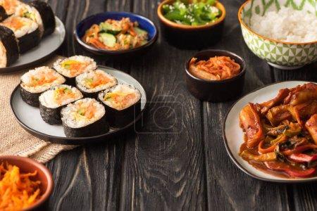Photo pour Recentrage sélectif du gimbap traditionnel près de savoureux plats coréens sur une surface en bois - image libre de droit