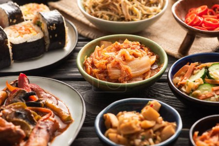 Photo for Selective focus of traditional spicy kimchi and topokki near tasty korean dishes on wooden surface - Royalty Free Image