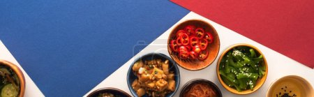 Photo for Horizontal concept of bowls with korean spicy side dishes and oil on blue, crimson and white - Royalty Free Image