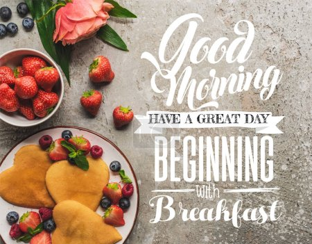 Photo pour Vue de dessus des crêpes en forme de coeur avec des baies sur la surface en béton gris avec rose fleurie, bonjour, avoir un excellent début avec illustration de petit déjeuner - image libre de droit