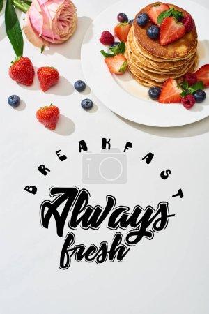 Photo pour Vue de dessus de délicieuses crêpes aux bleuets et fraises sur assiette près de rose fleur sur marbre surface blanche, petit déjeuner illustration toujours fraîche - image libre de droit