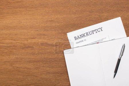 Photo pour Vue du haut du papier de faillite et carnet vierge avec stylo sur fond en bois - image libre de droit