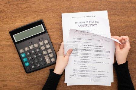 Photo pour Vue en coupe d'une femme avec des documents de faillite près d'une calculatrice sur fond de bois - image libre de droit