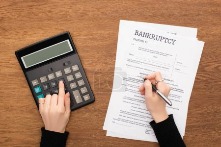 Photo for Cropped view of woman filling in bankruptcy form and using calculator on wooden background - Royalty Free Image