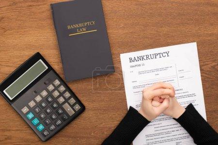 Photo pour Vue en coupe d'une femme serrée les mains sur un papier de faillite près d'un livre de droit de la faillite et d'une calculatrice sur fond de bois - image libre de droit