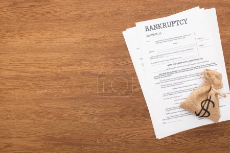 Photo for Top view of bankruptcy papers and money bag on wooden background - Royalty Free Image