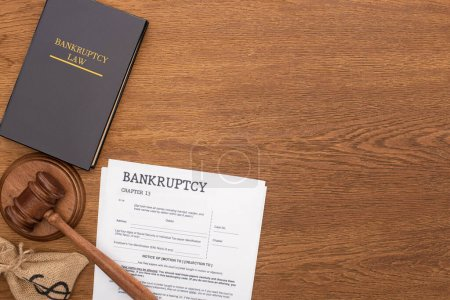 Photo pour Vue du haut du livre de droit de la faillite, documents, sac d'argent et marteau sur fond en bois - image libre de droit