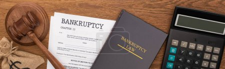 Photo for Top view of calculator, bankruptcy law book, documents, money bag and gavel on wooden background, panoramic shot - Royalty Free Image