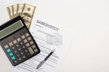 top view of bankruptcy paper with pen, money and calculator on white background