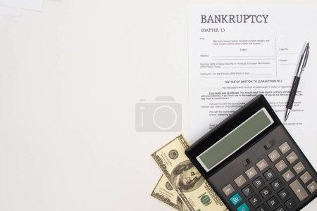 Photo pour Vue du dessus du papier de faillite avec stylo, argent et calculatrice sur fond blanc - image libre de droit