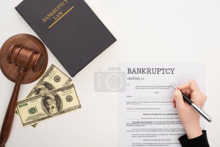 Photo pour Vue recadrée de femme remplissant le formulaire de faillite avec stylo près de l'argent, marteau et livre de droit de la faillite sur fond blanc - image libre de droit