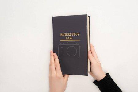 Photo pour Vue partielle d'une femme détenant un livre sur le droit de la faillite - image libre de droit