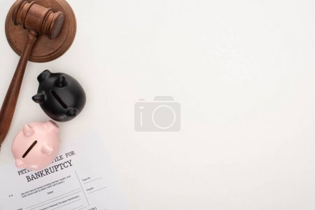 Photo for Top view of bankruptcy petition paper, gavel, piggy banks on white background - Royalty Free Image