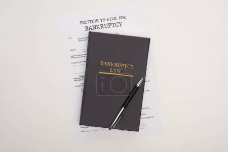 Photo for Top view of bankruptcy paper, law book and pen on white background - Royalty Free Image