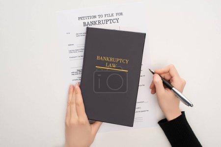 Photo pour Vue recadrée de la femme avec du papier de faillite, livre de loi et stylo sur fond blanc - image libre de droit