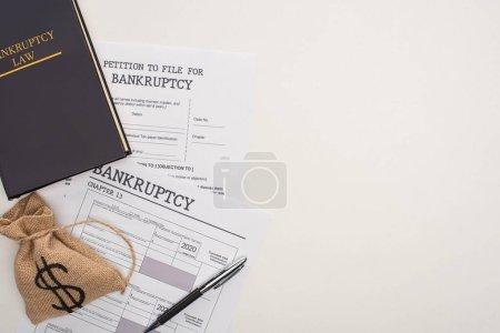 Photo pour Top view of bankruptcy papers, law book, money bag on white background - image libre de droit