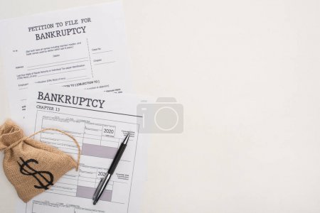 Photo for Top view of bankruptcy papers, money bag on white background - Royalty Free Image