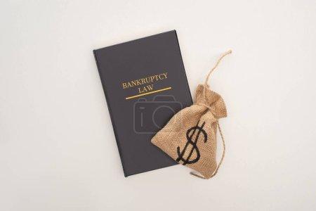 Photo pour Vue du haut du livre de droit de la faillite et sac d'argent sur fond blanc - image libre de droit