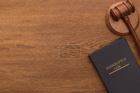 Photo pour Vue du haut du livre de droit de la faillite et marteau sur fond en bois - image libre de droit