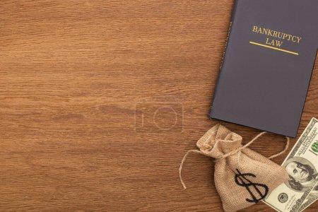 vista superior del dinero y el libro de leyes de bancarrota sobre fondo de madera