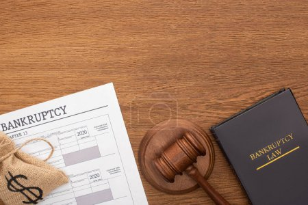 Photo pour Top view of money bag, bankruptcy paper, law book and gavel on wooden background - image libre de droit