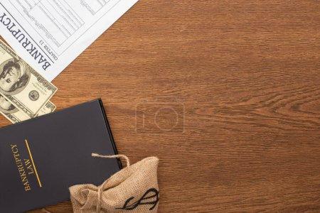 Photo pour Top view of bankruptcy paper, law book and money on wooden background - image libre de droit
