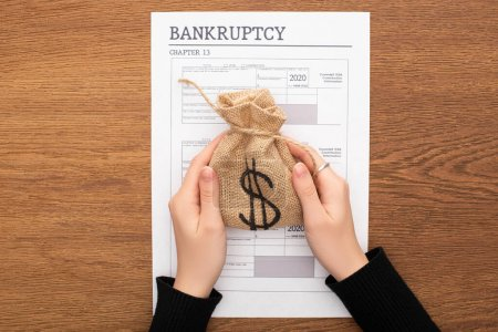 Photo pour Crochet vue d'une femme tenant un sac d'argent près du papier de faillite sur fond de bois - image libre de droit