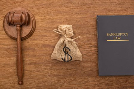 Photo pour Top view of bankruptcy law book, money bag and gavel on wooden background - image libre de droit