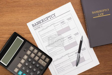 Photo pour Top view of bankruptcy paper, law book and calculator on wooden background - image libre de droit