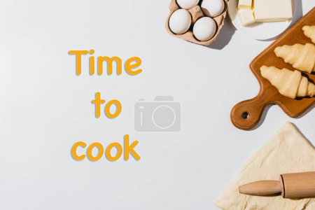 Photo for Top view of fresh raw croissants on wooden cutting board near rolling pin, butter and eggs on white background with time to cook lettering - Royalty Free Image