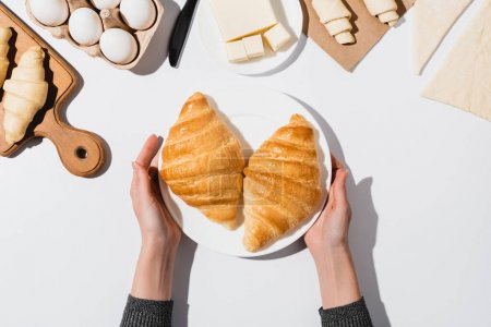 cropped view of woman holding plate with baked croissants on white background