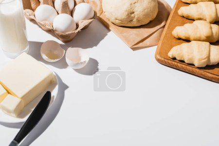 Photo for Fresh croissants on wooden cutting board near raw dough, milk, butter and eggs on white background - Royalty Free Image