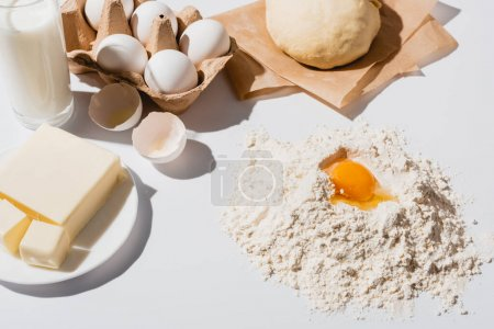 Photo for Fresh raw dough, flour, milk, butter and eggs on white background - Royalty Free Image