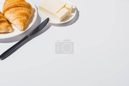 Photo pour Savoureux croissants frais cuits au four sur assiette près du beurre avec couteau sur fond blanc - image libre de droit
